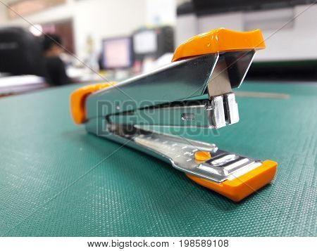 A stapler on table with blurred office background.