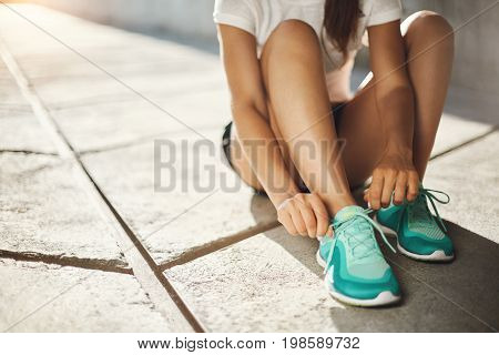 Sport is the way of life. Close-up of runner sneakers tying laces getting ready to run.