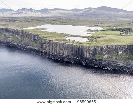 Cinematic aerial shot of the dramatic coastline at the cliffs close to the famous Kilt Rock waterfall , Skye - Scotland