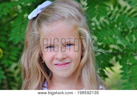 A cute blonde little girl is smiling at the camera.