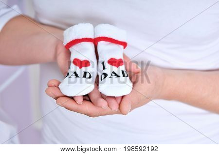 Pregnant woman holding a pair of cute baby boots