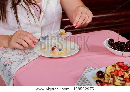 food, dessert and people concept - close up of woman eating waffle with strawberry