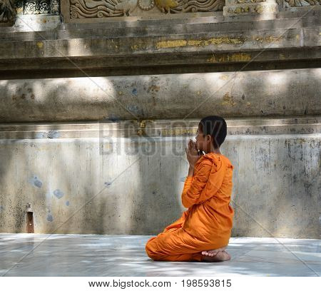 A novice monk praying at Buddhist temple.