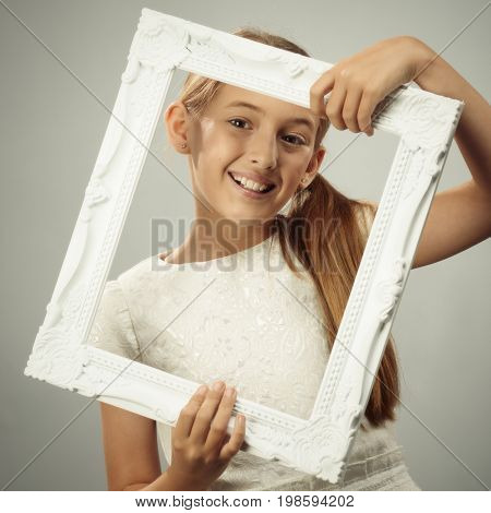 Smiling young girl looking though a white photo frame