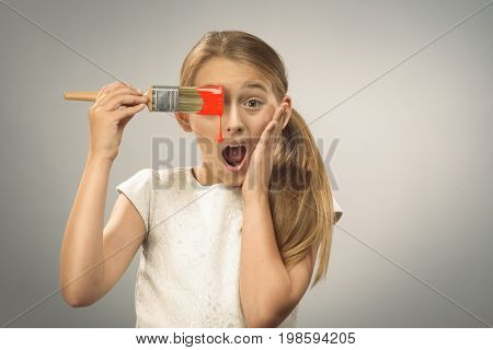 Young girl holding paintbrush with dripping red pain on a plain background with plenty of copy space