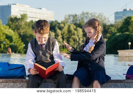 Girl in school clothes distracting a student from reading a book