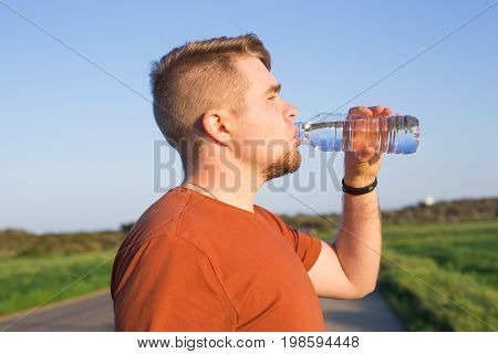 Closeup portrait of young guy drinking water from bottle on a hot sunny day.