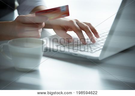 Business woman holding credit card and using laptop. Online pay.