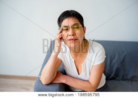 Elderly woman is suffering from a headache