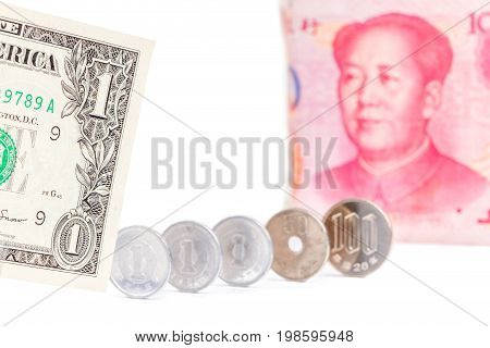 One US dollar bill with blurred Chinese yuan banknote and Japanese yen coins on white background world economy concept.