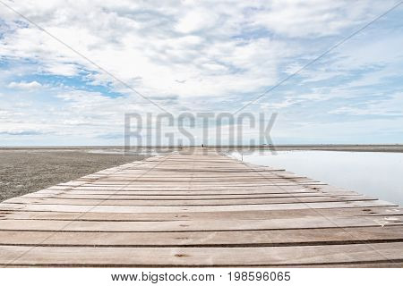 Wood Bridge Extends Into The Sea At Ebb Tide Time With Cloudy Sky