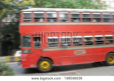 red double-Decker bus rides on the road. blurred