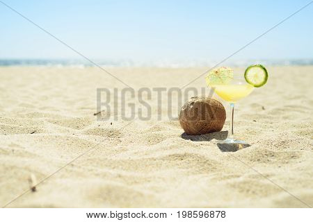 Cocktail glass and coconut on sand on the beach, with ocean on background. Perfect vacation.