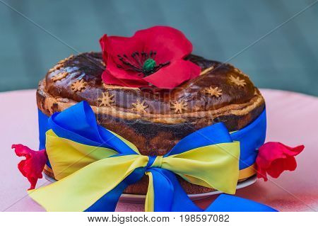 Ukrainian homemade festive bread decorated with red poppies and yellow-blue ribbon which symbolizes the Ukrainian flag