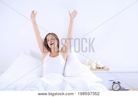 An attractive young woman stretching in bed after waking up