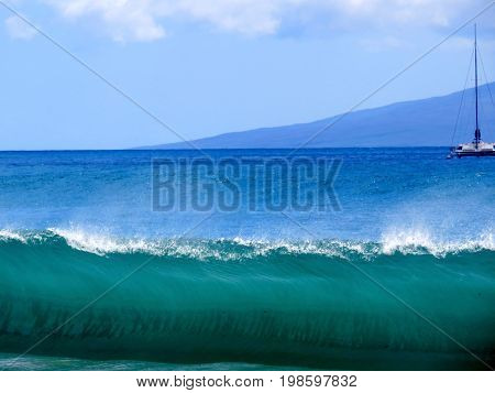 Large Wave Cresting on the shore of Maui with Boat and Island in Background.