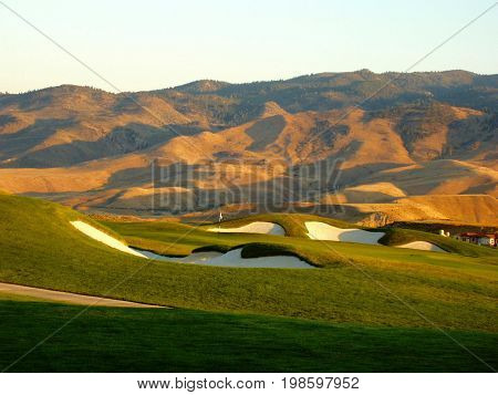 Golf Green in Front of Mountains at Sunset.