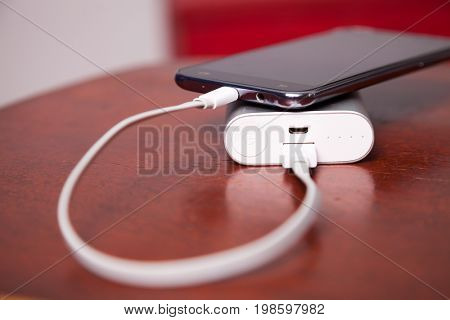Mobile Phone Charging With Power Bank on wooden table, USB cord pluged