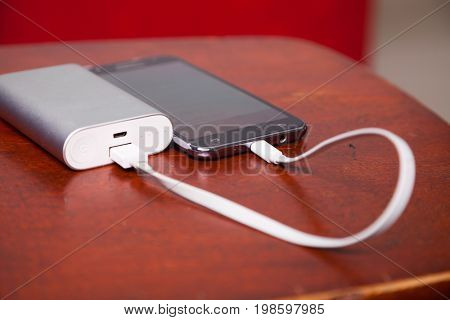 Mobile Phone Charging With Power Bank on wooden table