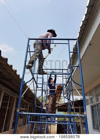 CHIANG RAI THAILAND - MARCH 29 : unidentified workers repairing or changing roof of Thai protestant church on March 29 2017 in Chiang rai Thailand.