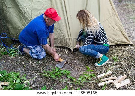 Sumy Ukraine - August 7 2017: Tourists putting up a tent in a camp. Putting up sturdy tent is an essential skill during camping activities.