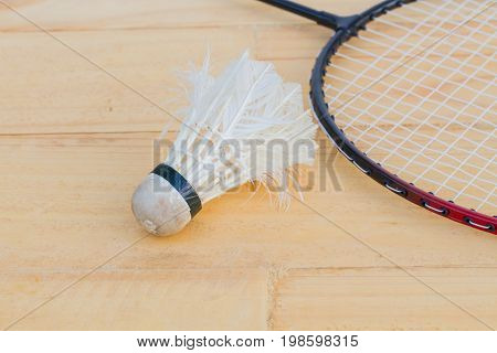 used shuttlecock and badminton racket on wooden background