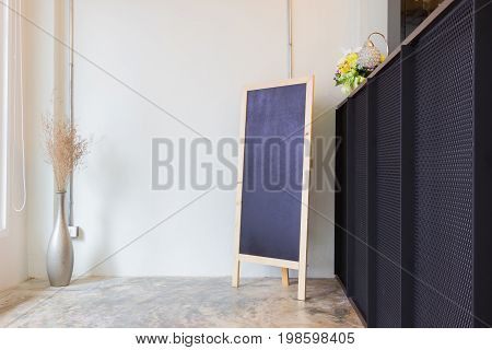 Blank cafe or restaurant menu blackboard on the wall with a vase and dry flowers