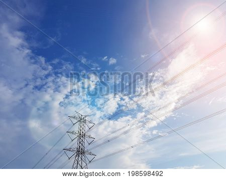 High-voltage tower with electric lines in cloudy blue sky background with lens flare