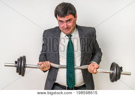 Businessman With Barbell Is Lifting Heavy Weight