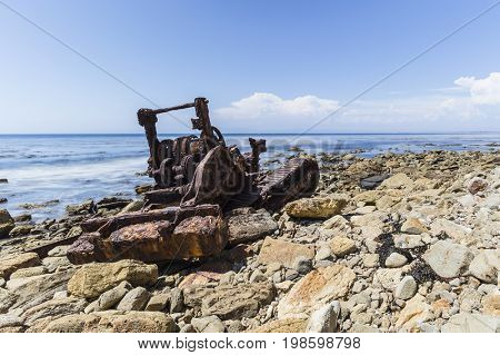 Rusty tractor from old shipwreck with motion blur waves on the Rancho Palos Verdes shoreline in Southern California.
