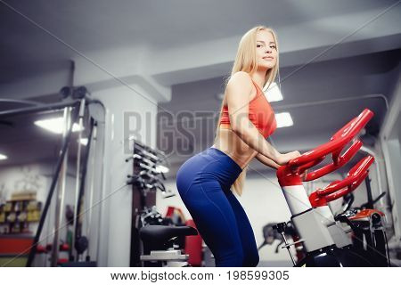 Girl blonde European appearance of a sport build on fitness bike in gym, in  background friends are a girlfriend. The concept of doing sports, maintaining form, advertising sports hall.