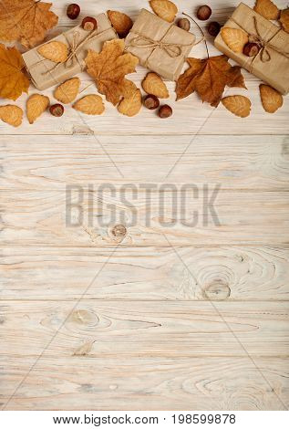 Flat lay frame of yellow leaves cookies in the form of leaves hazelnuts and gift boxes on a light wooden background. Selective focus.