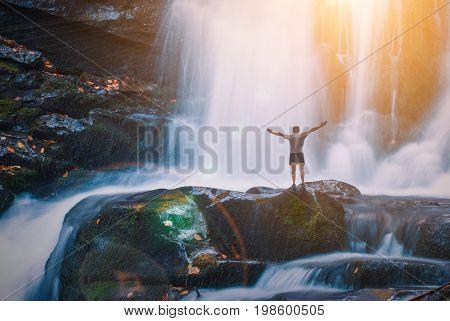 Man on a Great waterfall in a Carpathian mountains. Ukraine
