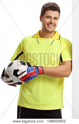 Goalkeeper with a football leaning against a wall isolated on white background