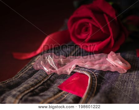 Low key of condom and red rose on pink background. Save sex Family plan and Valentine concept.