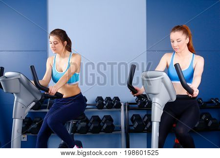 Group of people at the gym exercising on cross trainers. People at the gym
