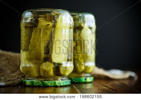 Home preservation. Canned in a glass jar ripe cucumber on a wooden table.