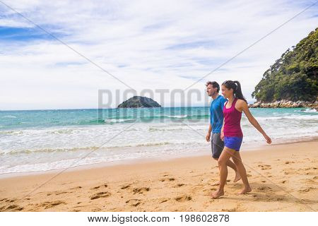 New Zealand beach couple hikers walking the coast track in Abel Tasman National Park. People tramping relaxing in nature outdoors.