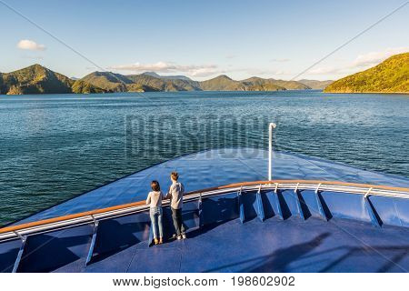 New Zealand cruise travel people enjoying nature view of ferry boat cruising in Marlborough sounds trip from Picton to Wellington, Cook strait crossing. Couple tourists watching sunset on deck.