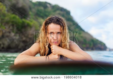 Happy girl in bikini have fun before surfing Surfer lie on surf board look at sunset sky. People in water sport adventure camp extreme activity on family summer beach vacation. Watersport background