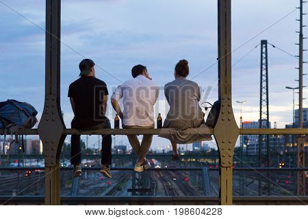 Group of friends sitting and hanging out on railway bridge with bottles of beer and watching the sunset over Munich urban city center.