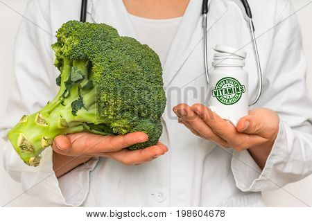 Female Doctor Compare Pile Of Pills With Fresh Broccoli