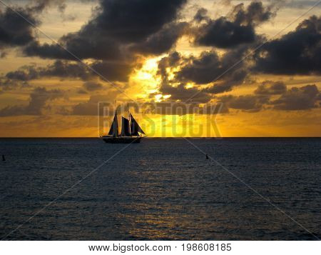 A sailing boat with three sails sailing in the sunset in Saint Martin