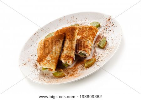 Crepes with kiwi and cream on white background