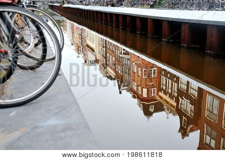 Scenic view of bicycle and canal with the building reflection in the water Amsterdam Holland Europe