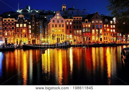 Scenic view of Amsterdam canal and buildings at night Netherlands Europe