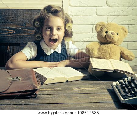 Kid choose career of journalist or writer. Small girl with curler in hair read book. Education and childhood. Child with briefcase and typewriter on table. Little baby secretary in cabinet or library. poster