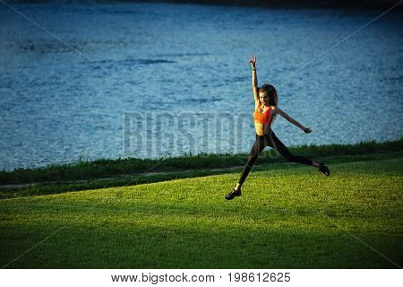 Coach or trainer at workout. Woman running on green grass. Girl sunny outdoor. Runner and success. Sport and sportswear fashion.
