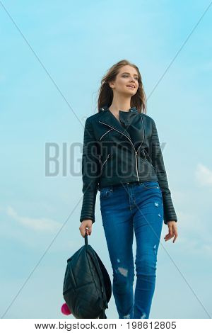 Fashion model on blue sky. Beauty and fashion. Woman with long hair. Sexy woman outdoor. Girl in leather jacket with backpack