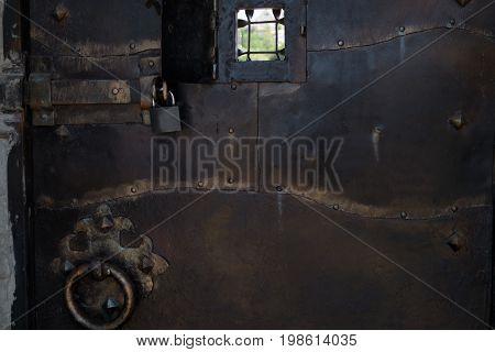 Window or peephole in the antique metal door. Guard concept.